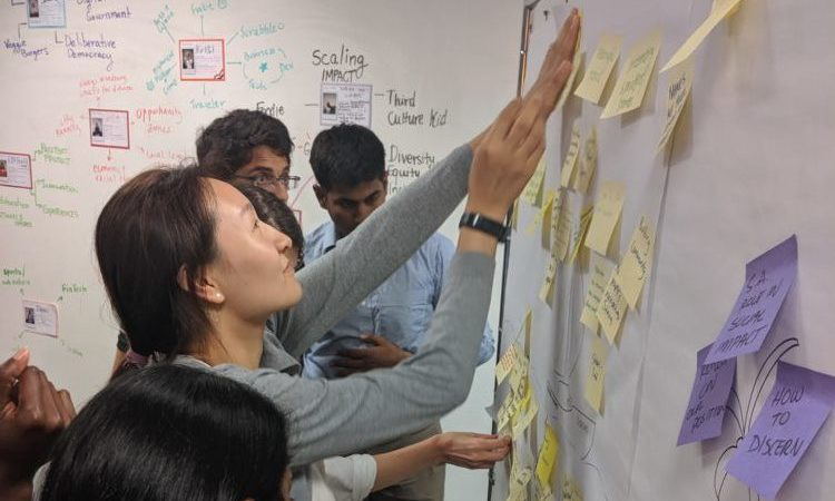 Students post ideas on a whiteboard