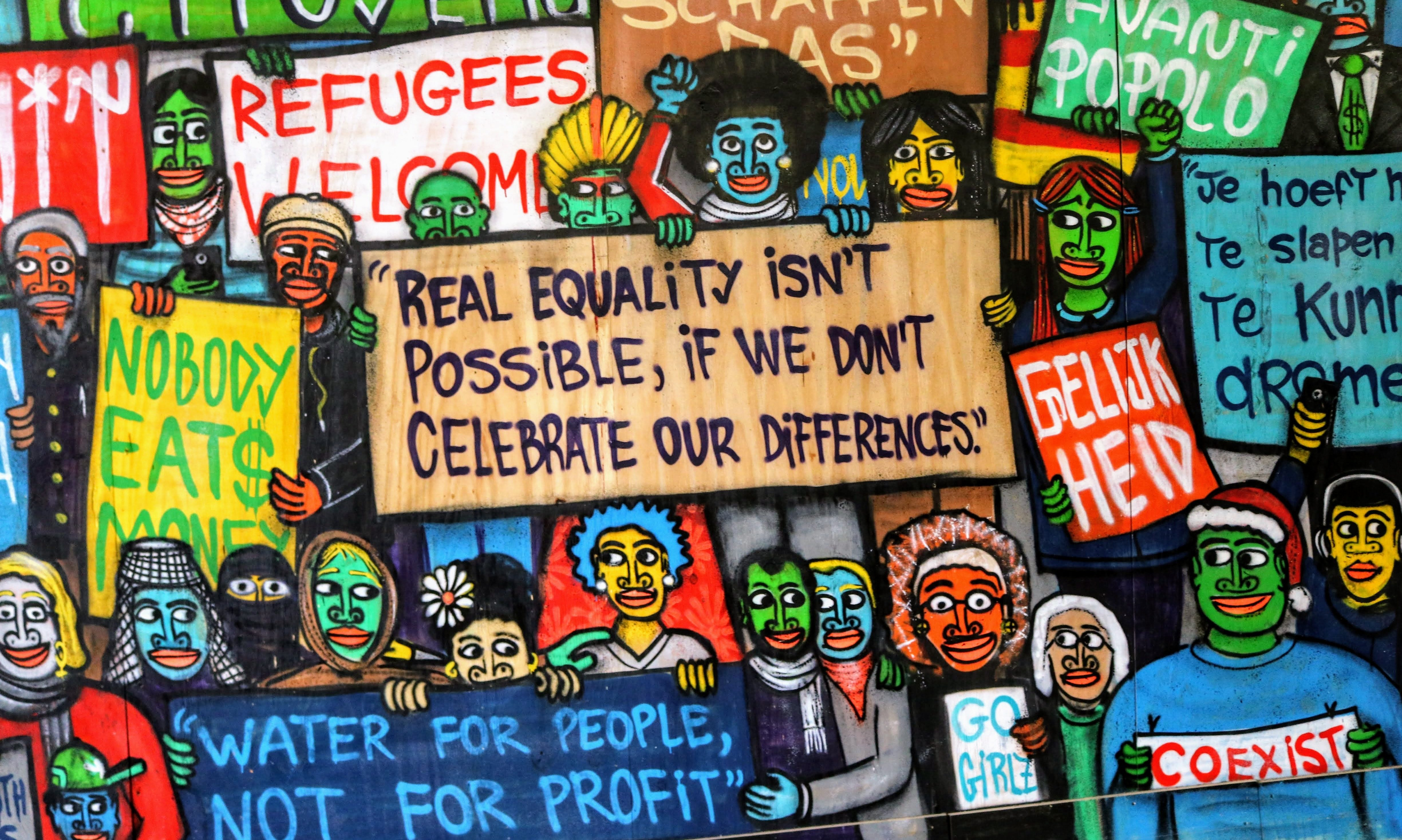 "Colorful grafitti saying ""Real equality isn't possible if we don't celebrate our differences"