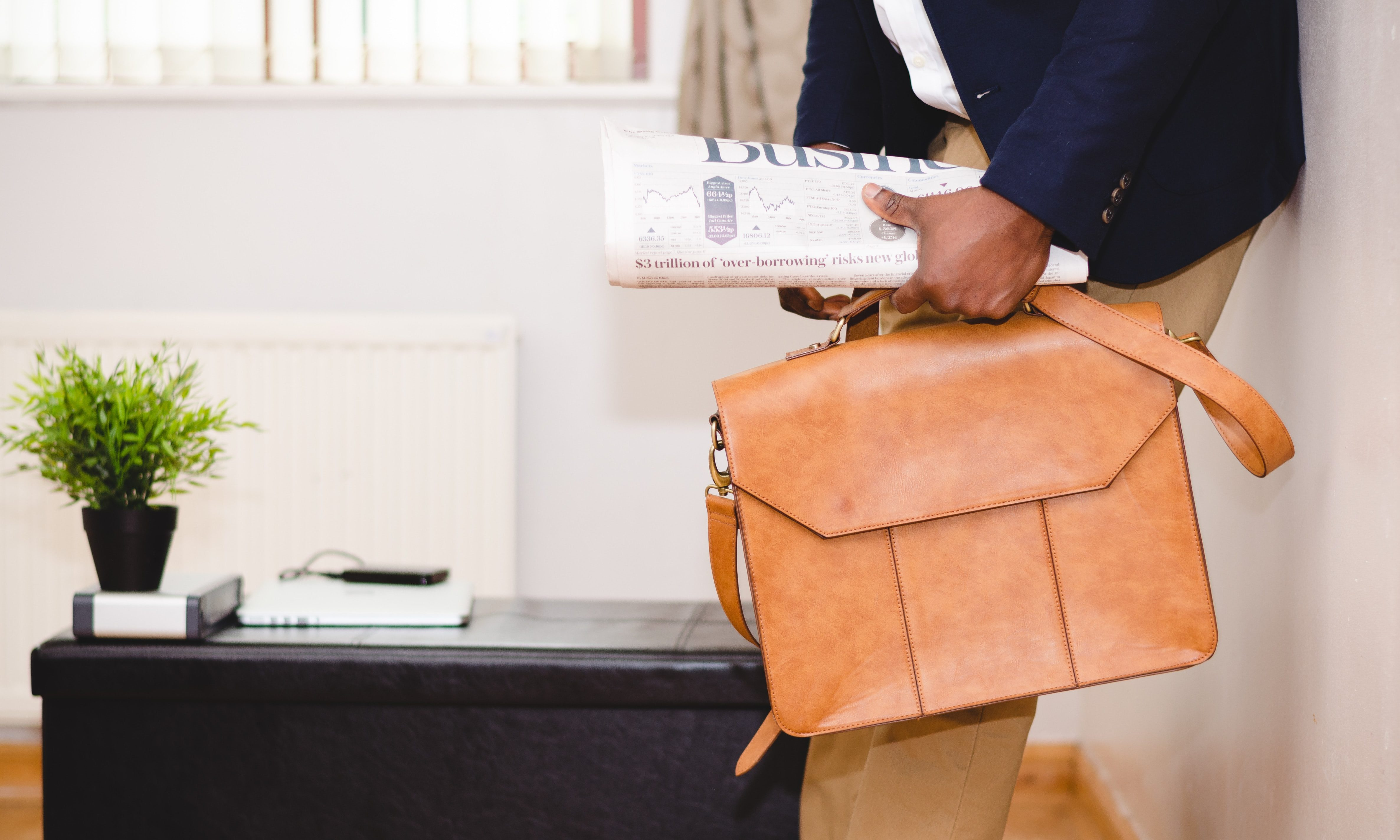 Man holding briefcase and newspaper