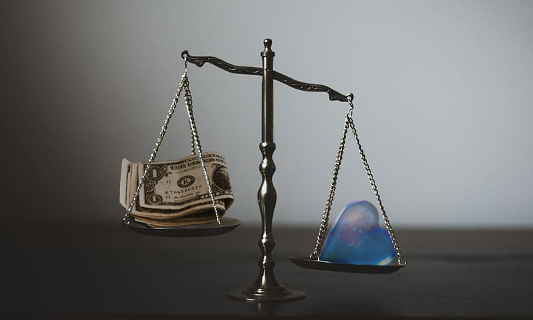 scales balancing cash and a blue glass heart