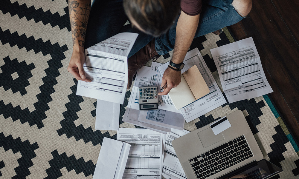 man sits on floor with pile of bills and computer