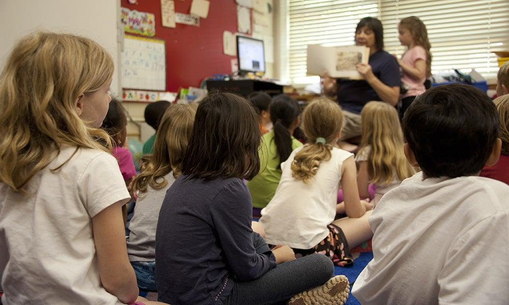 school kids sitting on floor in classroom