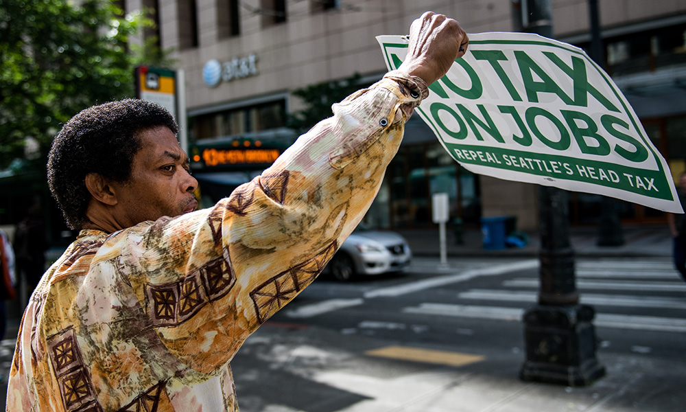 "African-American man stands on corner holding a ""No tax on jobs"" sign"