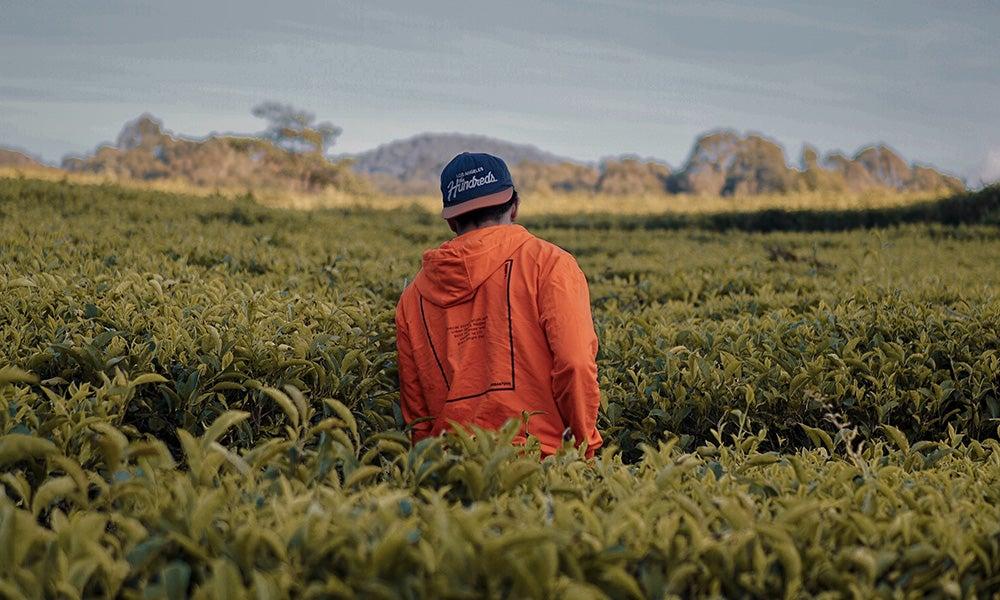 farmer in orange coat working in field
