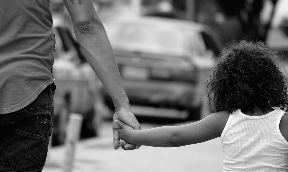 black and white image of father holding daughter's hand walking down city street