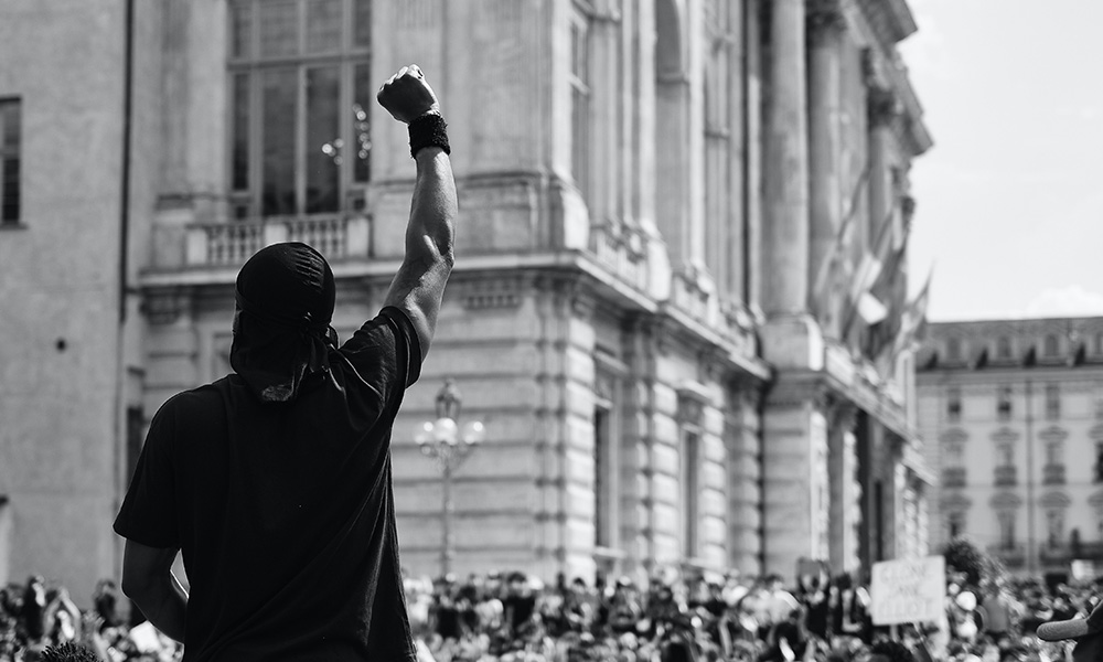 black and white photo of Black man with fist raised addressing large crowd