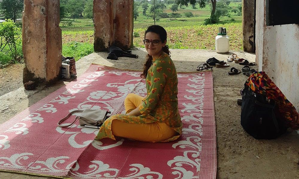 Woman sitting cross-legged on rug outside building