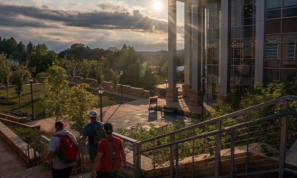students walk down brick step at sunset