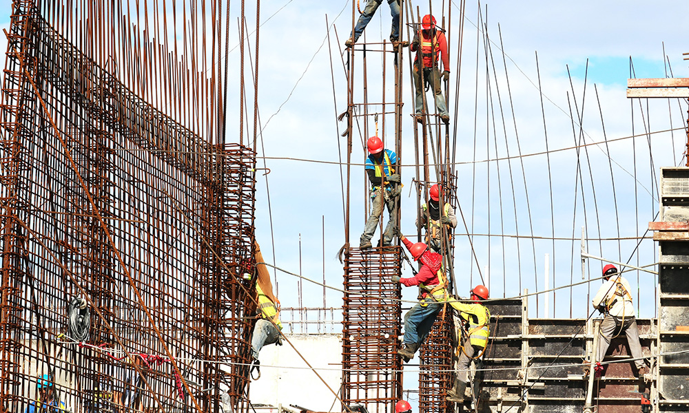 men climb scaffolding while doing construction work