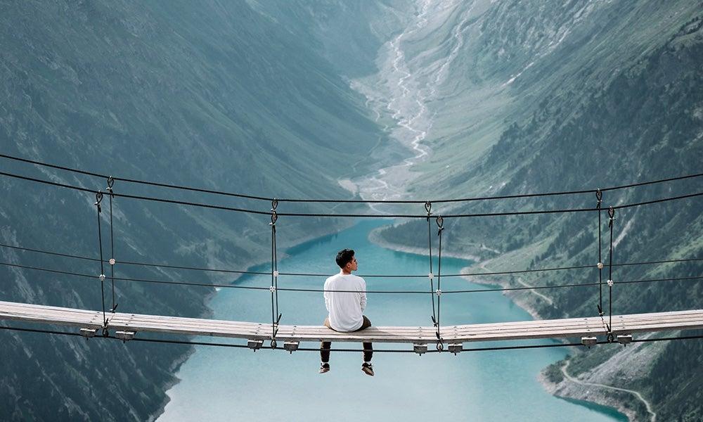 man sits in center of narrow bridge overlooking an alpine lake