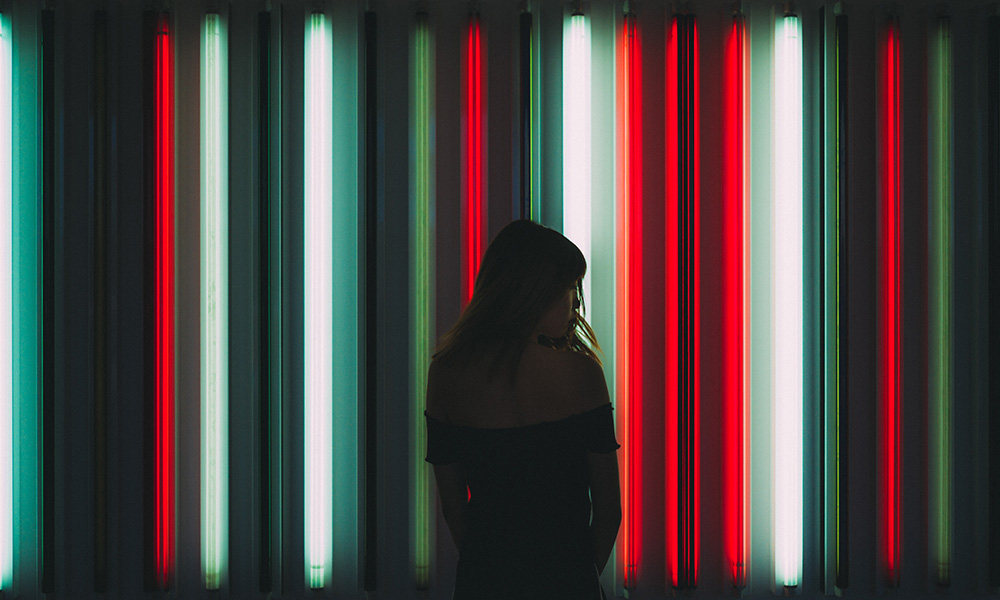 woman standing in front of red white and green neon tubes