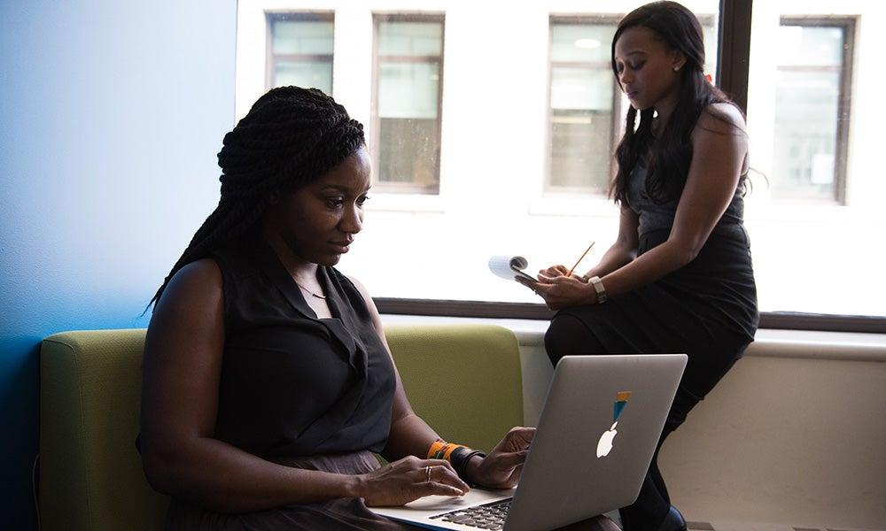 two Black women work on laptops