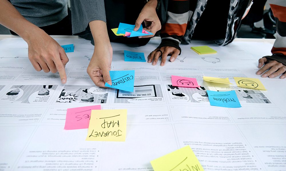 hands placing colored sticky notes on a user journey map