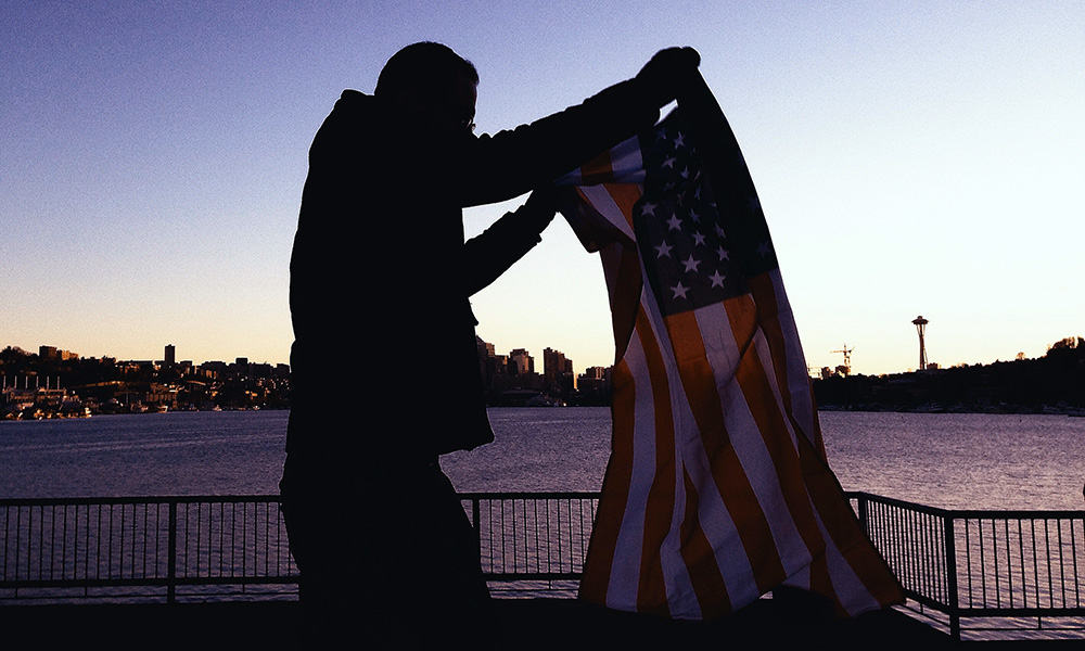 man in silhouette holding US flag