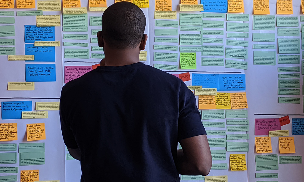 Young man looking at whiteboard with post-it notes