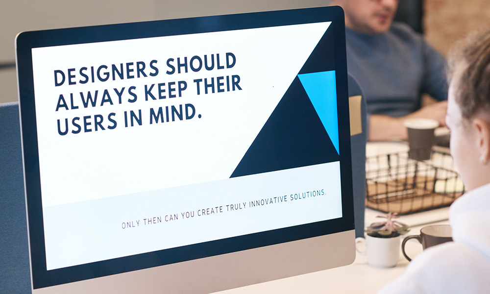 "man at computer with screen saying ""designers should always keep their users in mind."""