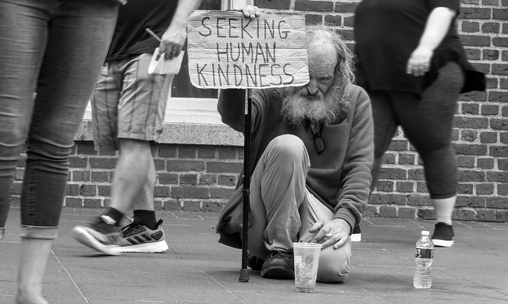 "black and white photo of man with sign reading ""seeking human kindness"""