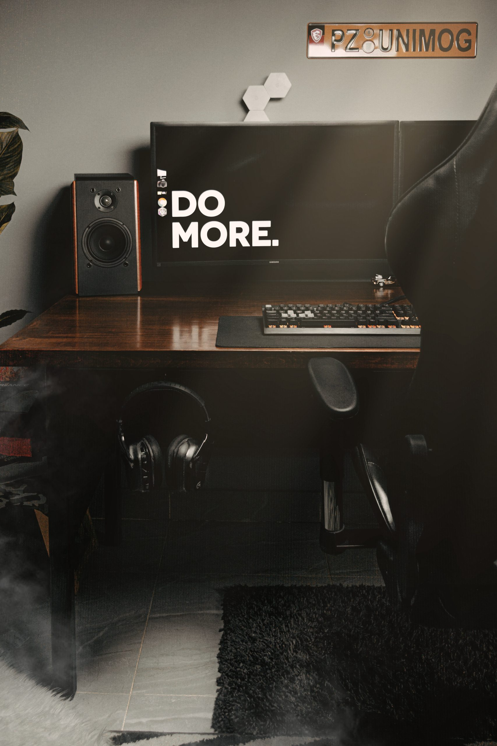"""A desk with a computer screen that reads """"Do more."""""""