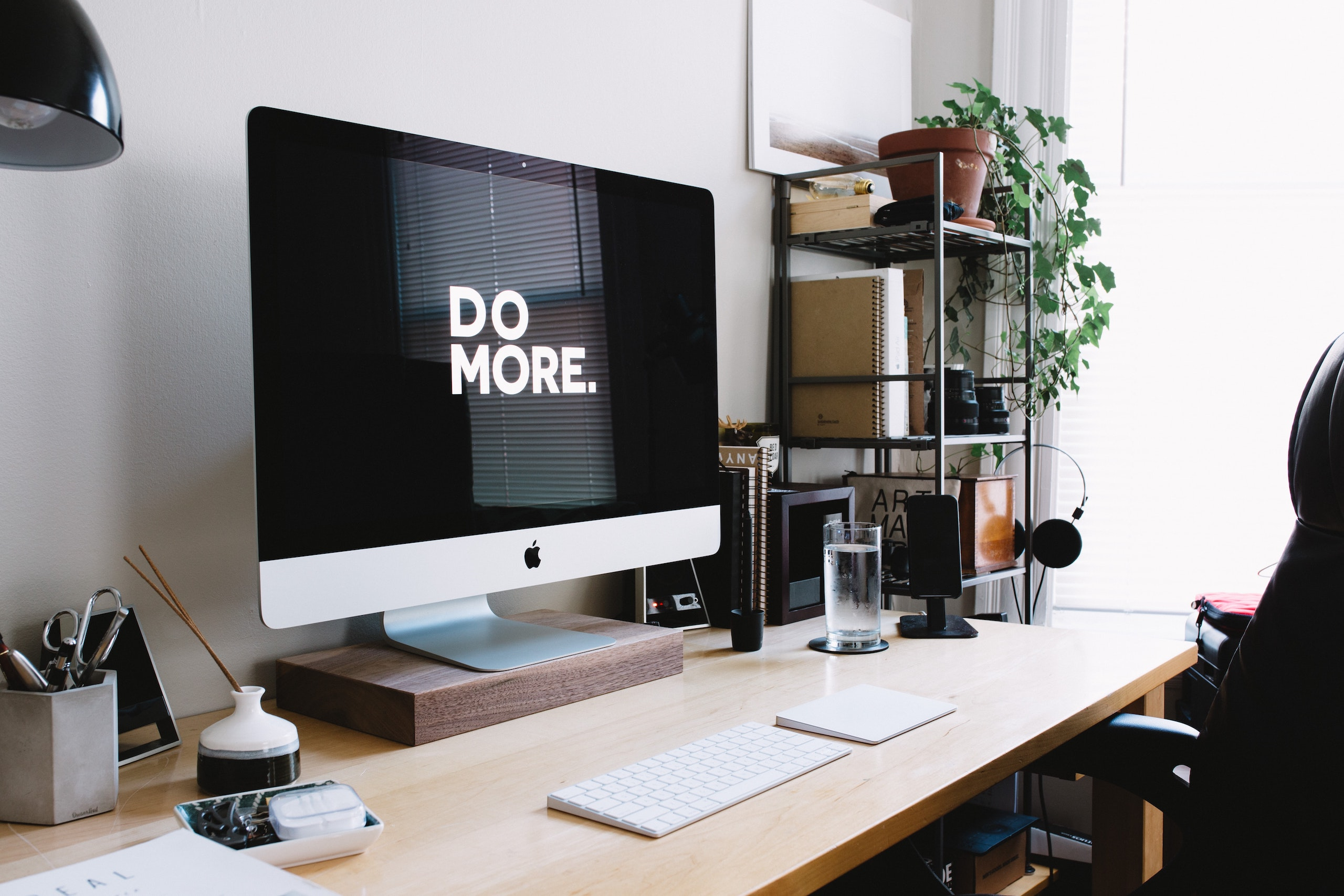 """Photo of a desk with a computer monitor that reads """"Do More."""""""